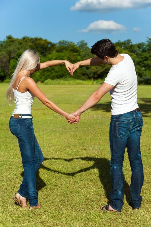 Pares novos que fazem o sinal do amor com braços. imagem de stock