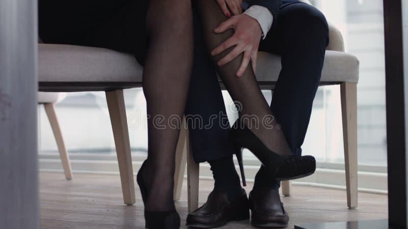 Pares novos que flertam com pés no restaurante sob a tabela imagem de stock