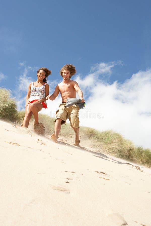Pares novos que funcionam abaixo da duna de areia imagens de stock royalty free