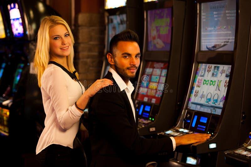 Pares novos que ganham no slot machine no casino foto de stock