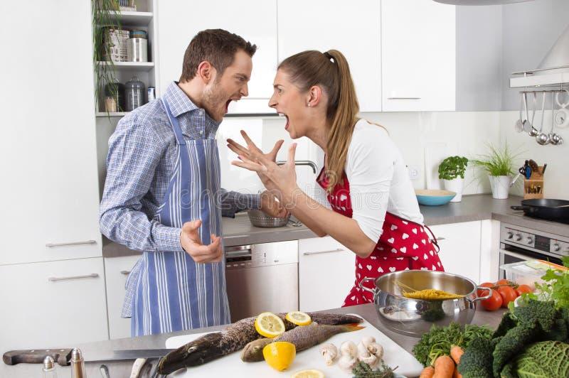 Pares novos que gritam em casa na cozinha foto de stock royalty free