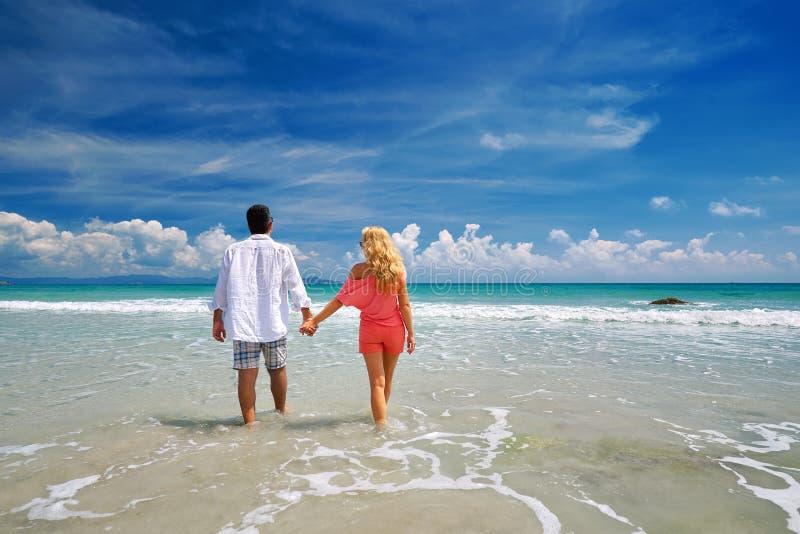 Pares novos que guardam as mãos na praia que aprecia o romance imagens de stock royalty free