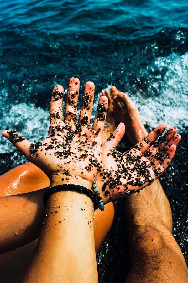 Pares novos que guardam as mãos perto do oceano fotos de stock royalty free