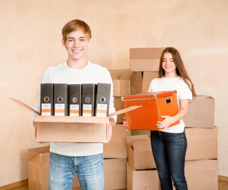 Pares novos que guardam caixas de cartão para mover-se em uma casa nova fotografia de stock
