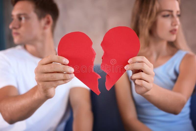Pares novos que guardam metades de coração quebrado no sofá em casa Problemas do relacionamento fotos de stock