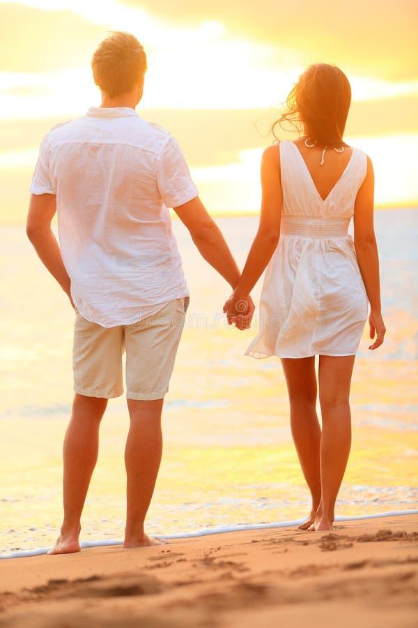 Pares novos que guardaram as mãos no por do sol da praia fotos de stock royalty free