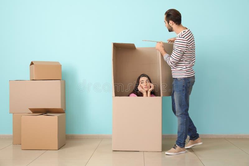 Pares novos que jogam com caixa enorme dentro Mover-se na casa nova imagem de stock royalty free