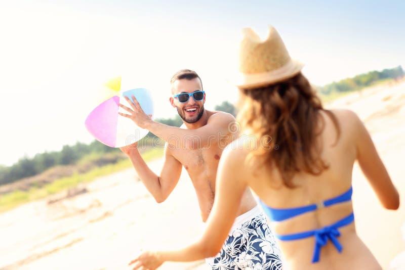 Pares novos que jogam com uma bola na praia foto de stock royalty free