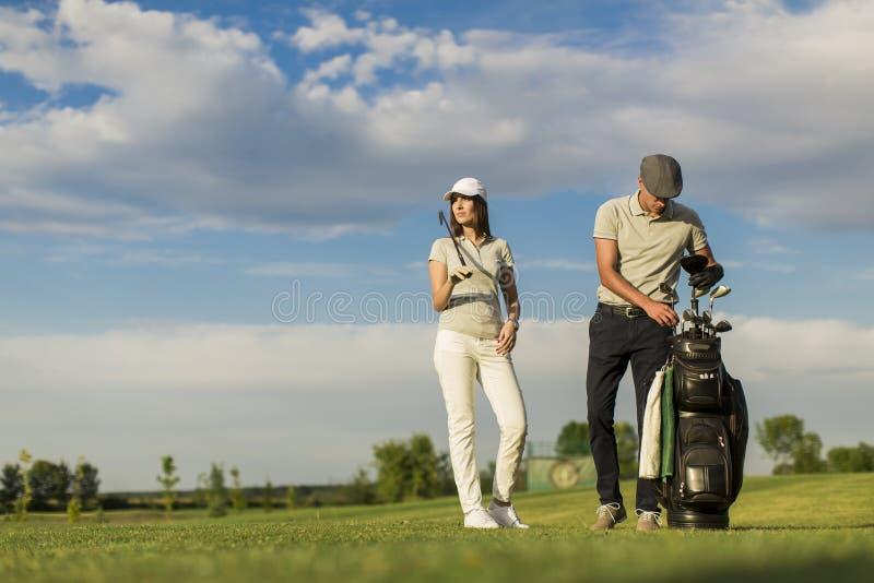 Pares novos que jogam o golfe imagem de stock royalty free