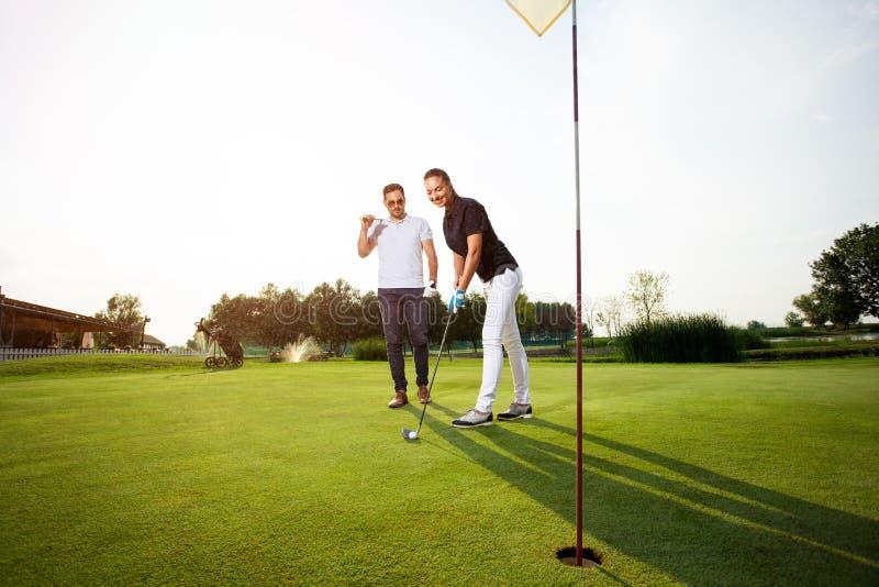 Pares novos que jogam o golfe - imagem imagem de stock royalty free