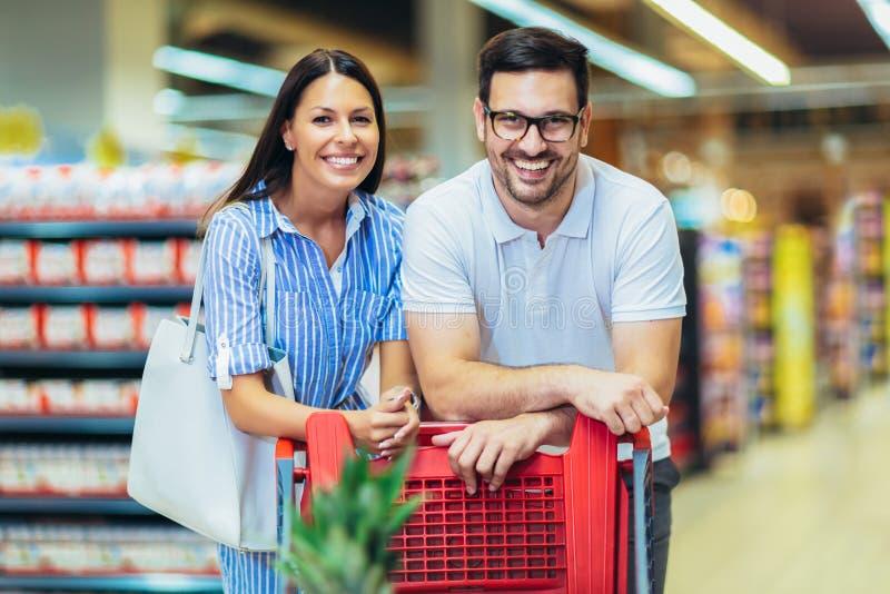 Pares novos que ligam-se entre si e que sorriem ao andar ao andar na despensa com carrinho de compras imagens de stock royalty free