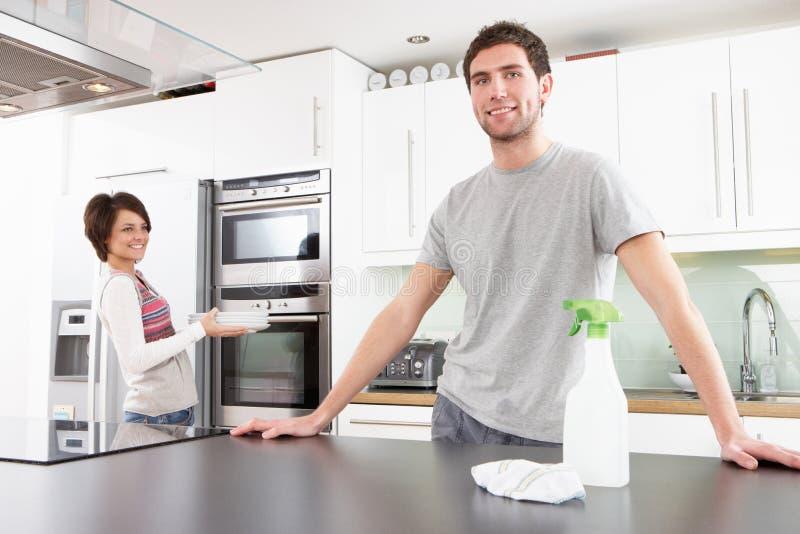 Pares novos que limpam a cozinha moderna foto de stock royalty free