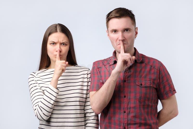 Pares novos que mostram um sinal do gesto do silêncio que põe o dedo na boca sobre o fundo branco imagens de stock