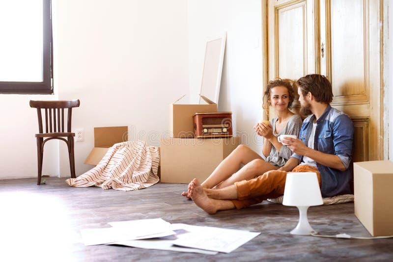 Pares novos que movem-se em uma casa nova imagens de stock royalty free