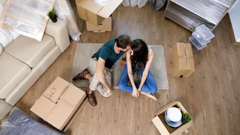Pares novos que movem-se na casa nova e que desembalam caixas do carboard imagem de stock