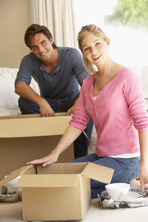 Pares novos que movem-se na casa nova que desembala caixas imagens de stock