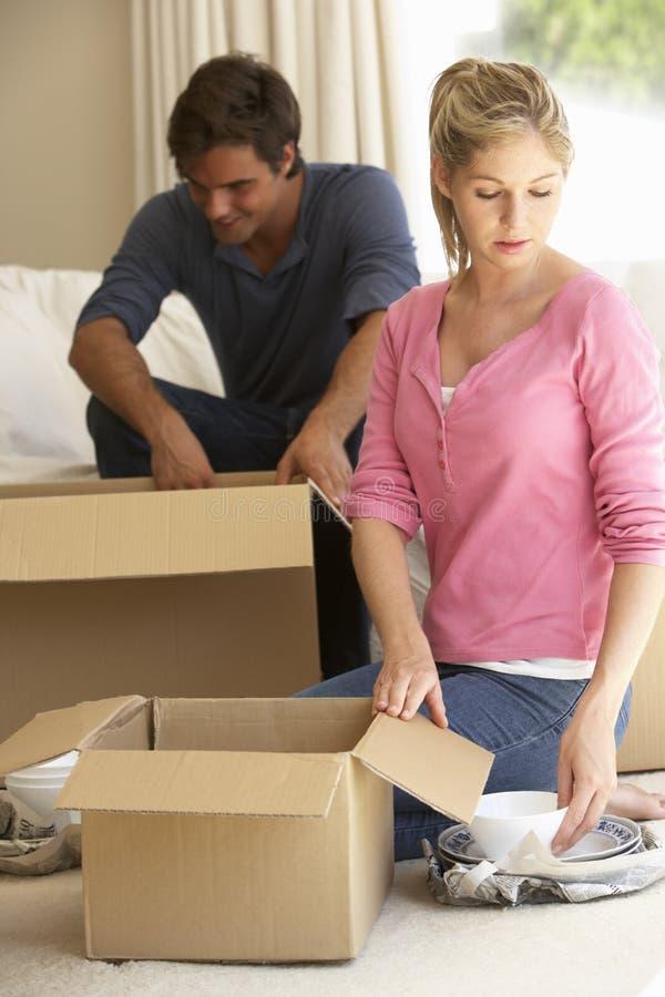 Pares novos que movem-se na casa nova que desembala caixas foto de stock
