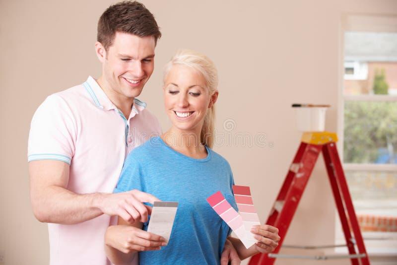 Pares novos que olham amostras de folha da pintura na casa nova fotos de stock royalty free