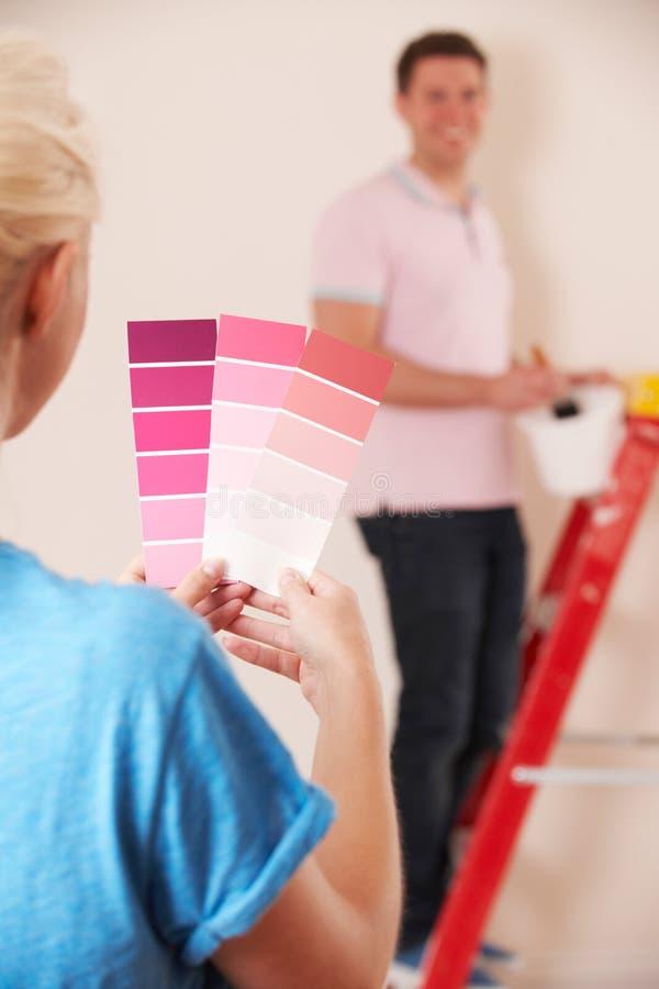 Pares novos que olham amostras de folha da pintura na casa nova imagem de stock royalty free