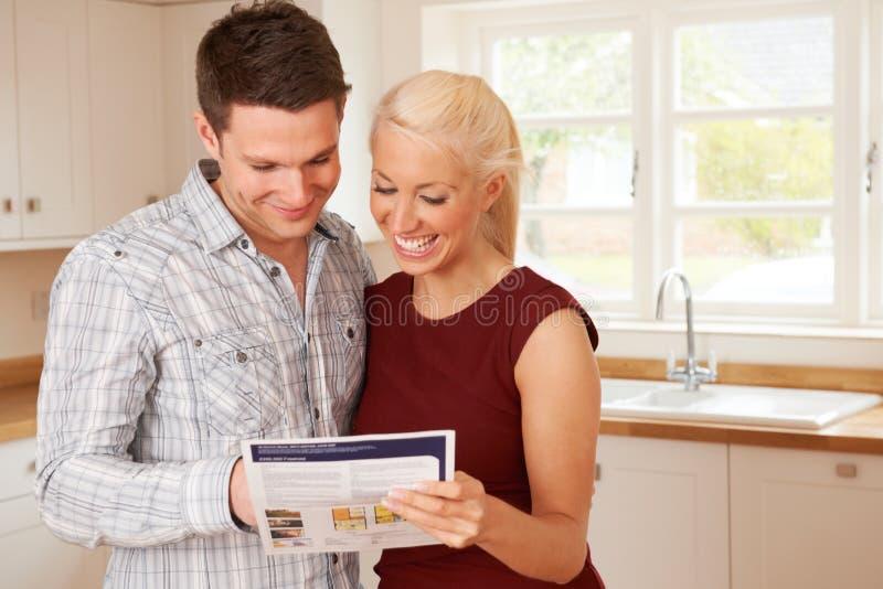 Pares novos que olham detalhes para a casa nova fotos de stock