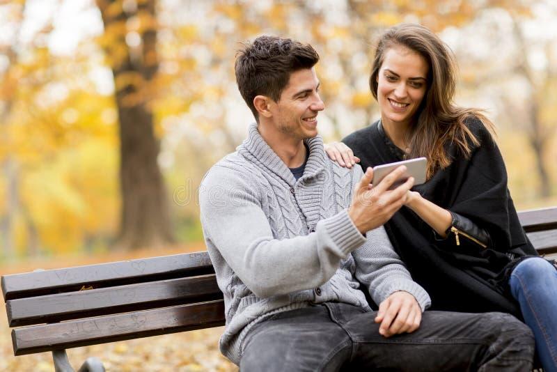 Pares novos que olham felizmente algo em um smartphone e em um sitt fotografia de stock