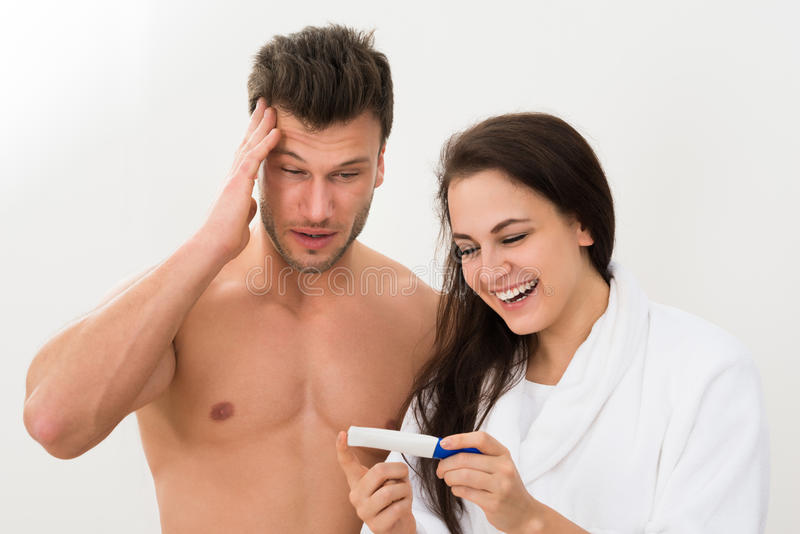 Pares novos que olham o teste de gravidez fotografia de stock