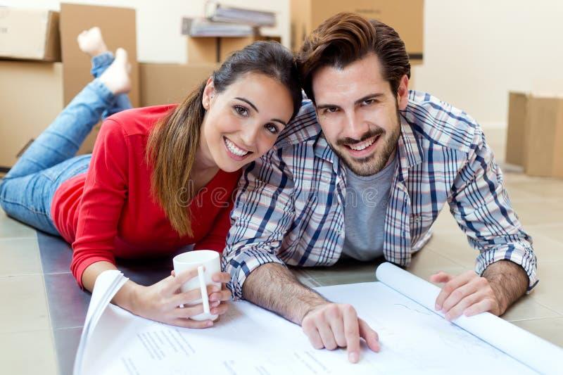 Pares novos que olham os modelos de sua casa nova fotos de stock royalty free