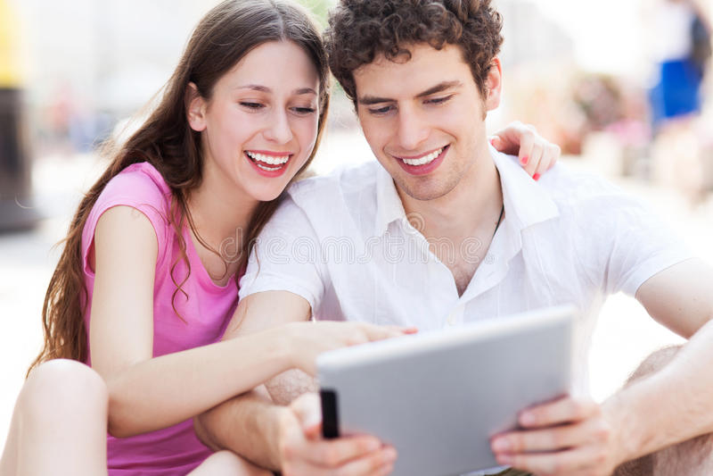 Pares novos que olham a tabuleta digital fotos de stock royalty free