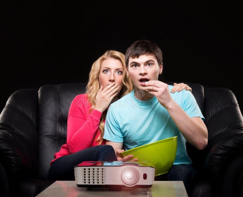Pares novos que olham um filme ao sentar-se em um sofá fotos de stock