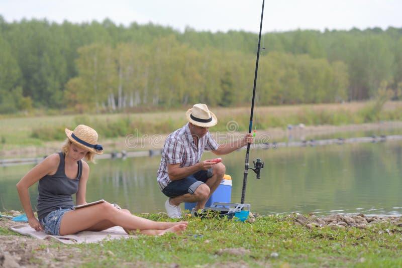 Pares novos que pescam ou que dobram na costa do lago fotos de stock royalty free