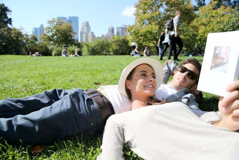 Pares novos que relaxam em Central Park que encontra-se na grama foto de stock