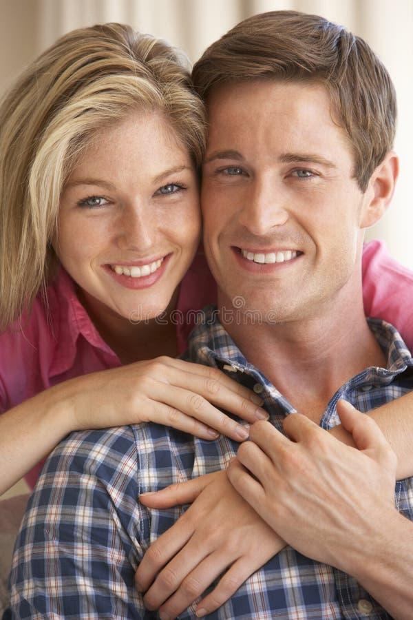 Pares novos que relaxam em Sofa Together At Home foto de stock royalty free