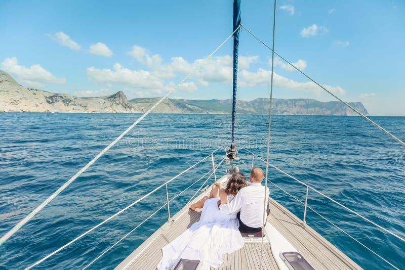 Pares novos que relaxam em um iate O homem rico feliz e uma mulher pelo barco privado têm a viagem do mar imagens de stock royalty free