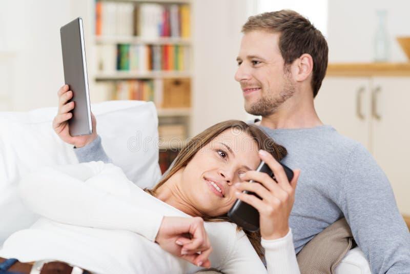 Pares novos que relaxam junto no sofá imagem de stock royalty free