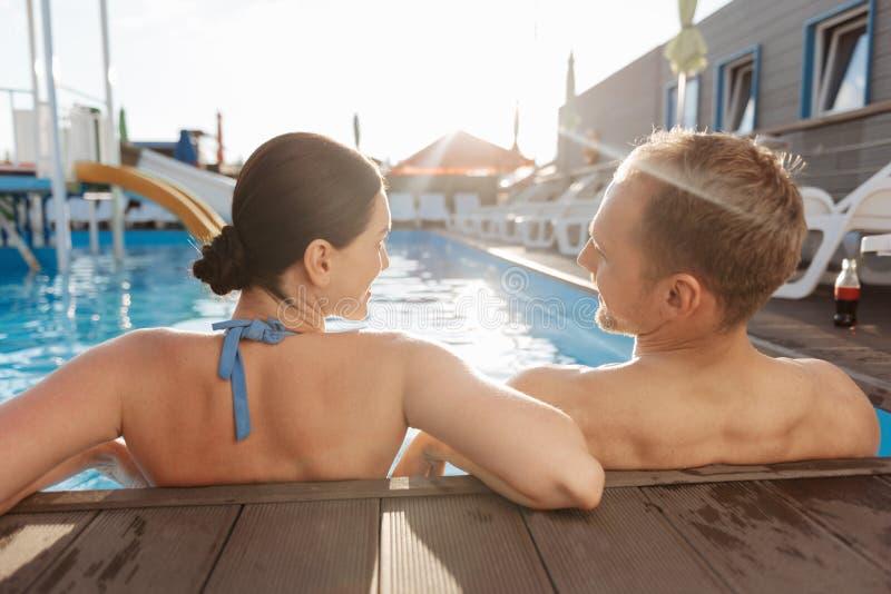 Pares novos que relaxam na piscina foto de stock