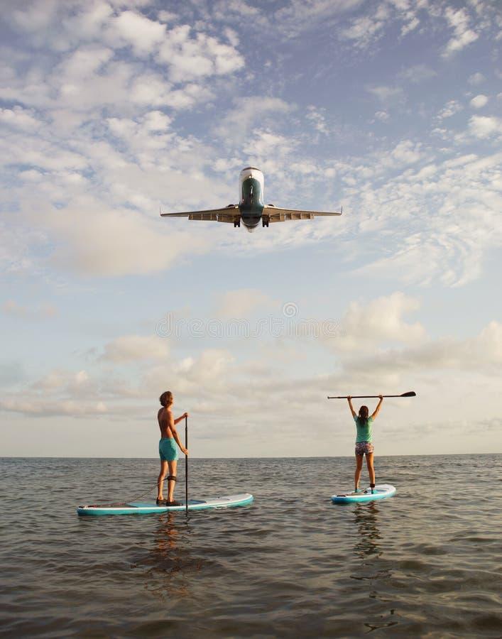 Pares novos que remam na placa do SUP com avião de aterrissagem fotos de stock royalty free