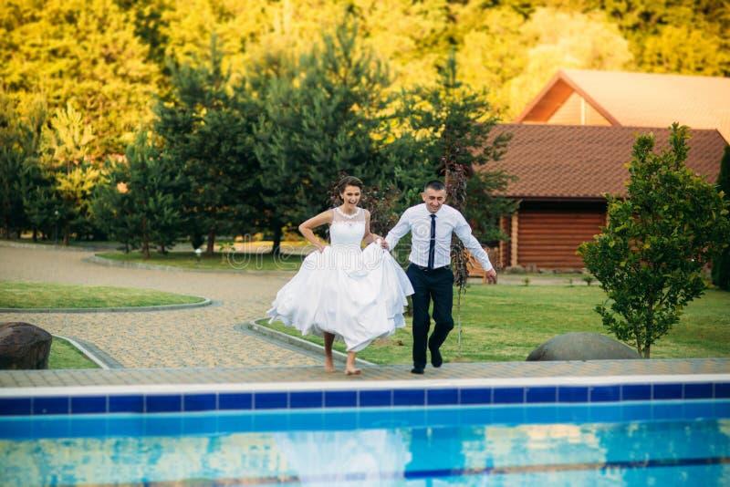 Pares novos que saltam na piscina em um terno do casamento e em um vestido de casamento Dia ensolarado imagem de stock