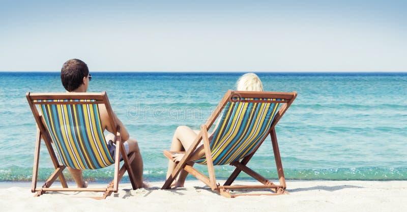 Pares novos que sentam-se em cadeiras de praia imagens de stock royalty free