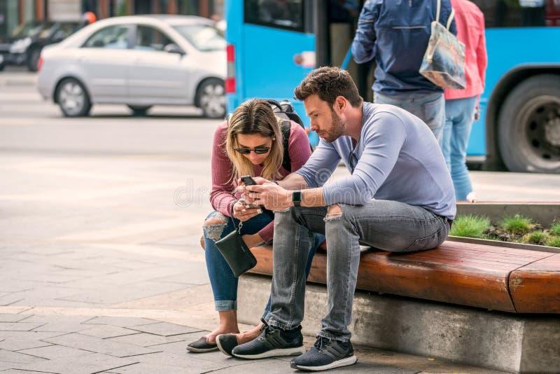 Pares novos que sentam-se em um banco que olha seus telefones celulares fotografia de stock royalty free