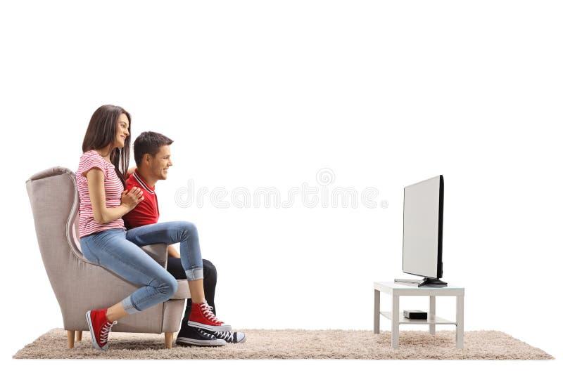 Pares novos que sentam-se em uma poltrona e em uma televisão de observação fotografia de stock