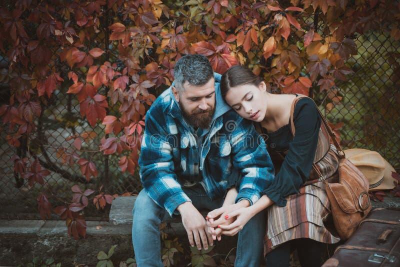 Pares novos que sentam-se fora no parque no dia bonito do outono Aventura, curso, turismo, caminhada e conceito dos povos - fotografia de stock