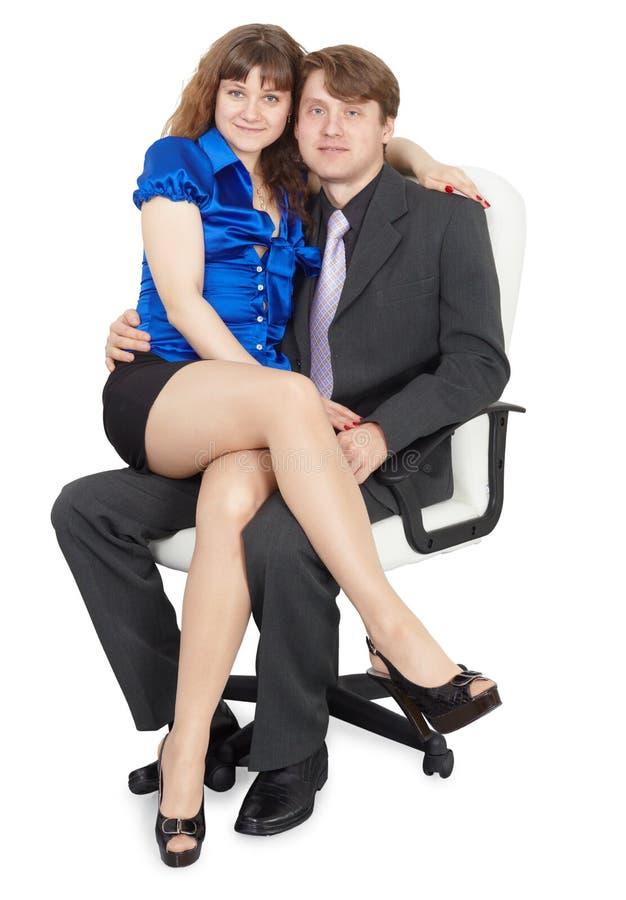Pares novos que sentam-se na cadeira do escritório imagem de stock