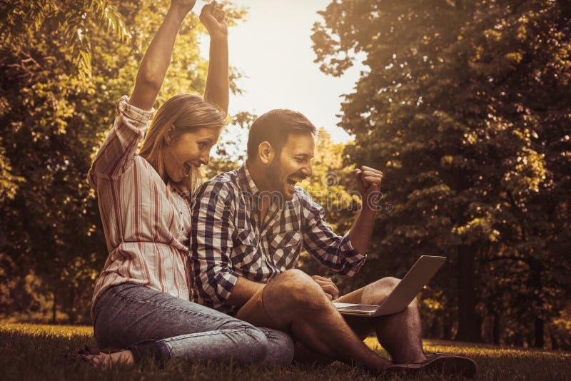 Pares novos que sentam-se na grama Pares felizes usando o portátil foto de stock