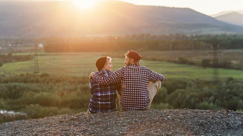 Pares novos que sentam-se na parte superior da montanha e que olham se no por do sol Pares delicados no por do sol romântico foto de stock royalty free