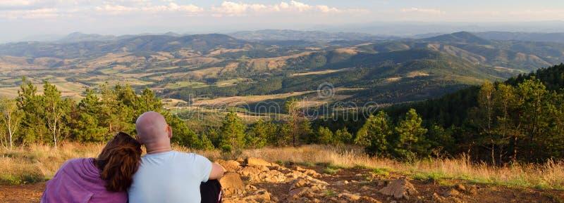 Pares novos que sentam-se na parte superior da montanha no dia de verão ensolarado fotografia de stock