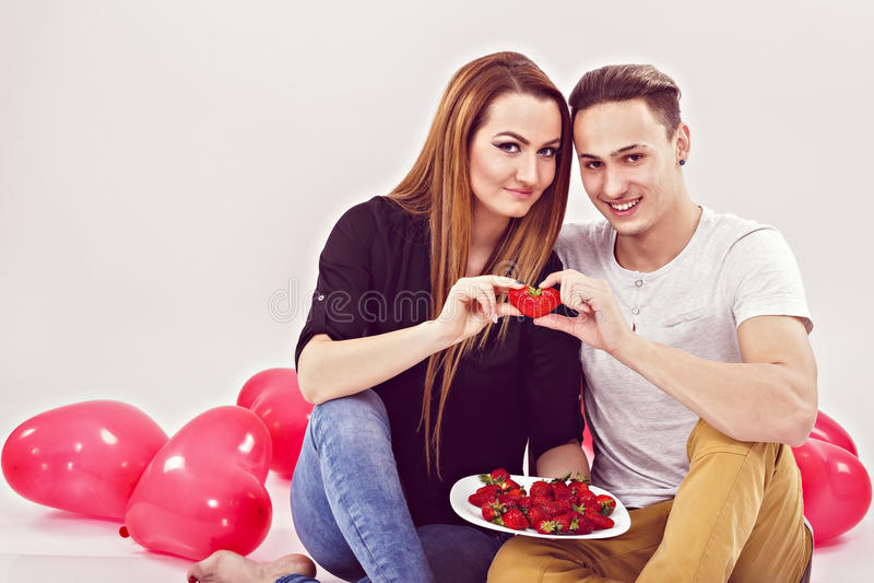 Pares novos que sentam-se no assoalho com os balões na forma de foto de stock royalty free