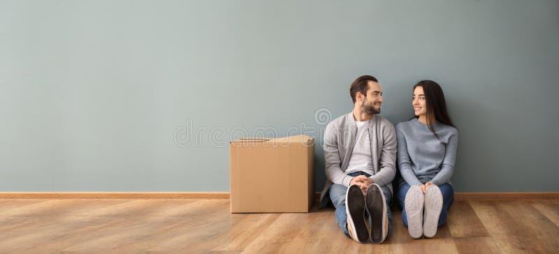 Pares novos que sentam-se no assoalho perto da caixa dentro Mover-se na casa nova imagens de stock