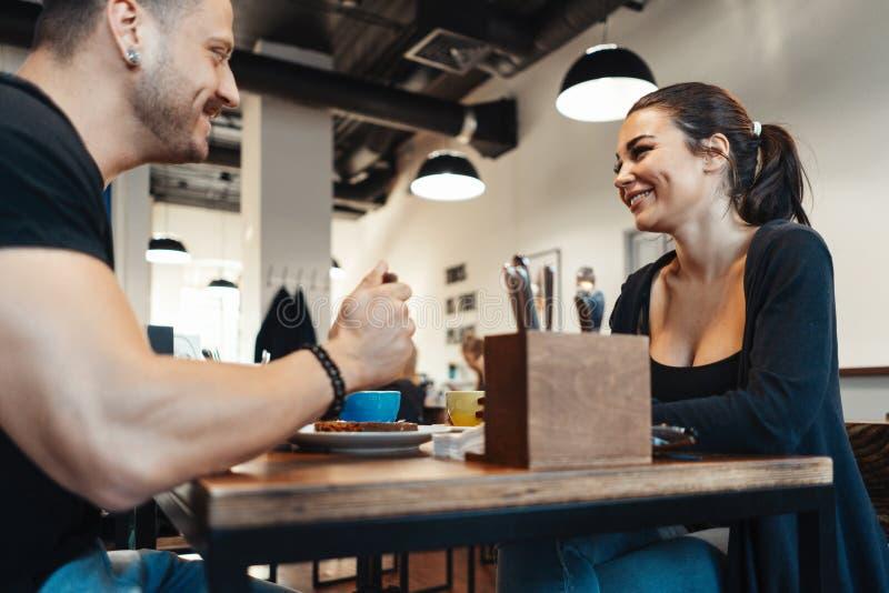 Pares novos que sentam-se no café na data, no café bebendo e comendo a sobremesa fotos de stock