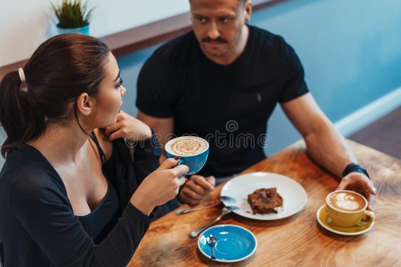 Pares novos que sentam-se no café na data, no café bebendo e comendo a sobremesa imagem de stock