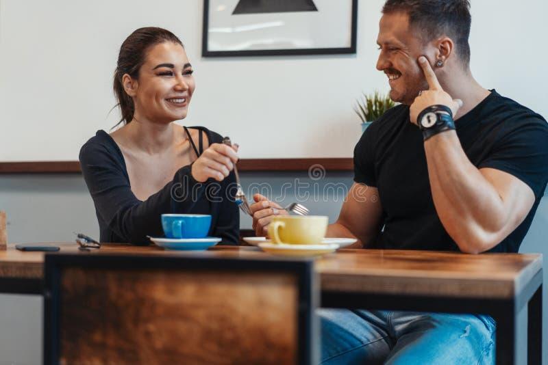 Pares novos que sentam-se no café na data, no café bebendo e comendo a sobremesa foto de stock royalty free